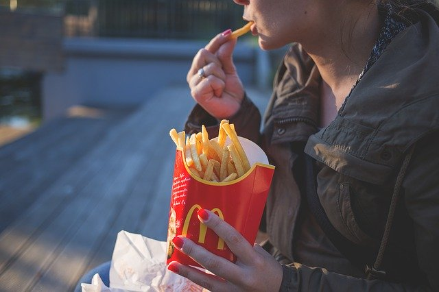 woman eating junk food, bad habits that make depression worse